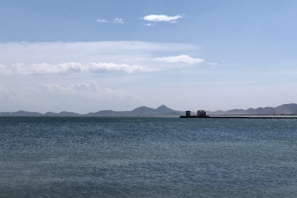 A jetty is seen in the sea, with mountains in the background.