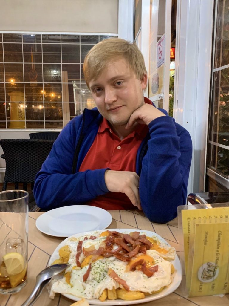 Me posing with a plate of huevos rotos.