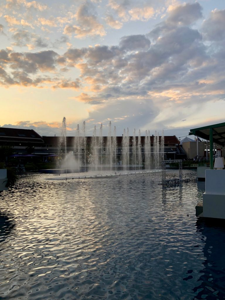 Fountains over a lake with a multicolour sunset sky in the background.