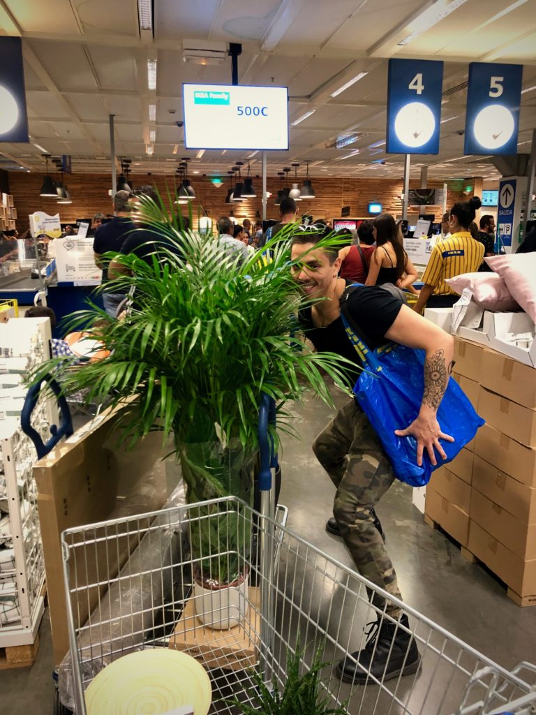 Bogar hides behind a large plant in IKEA.