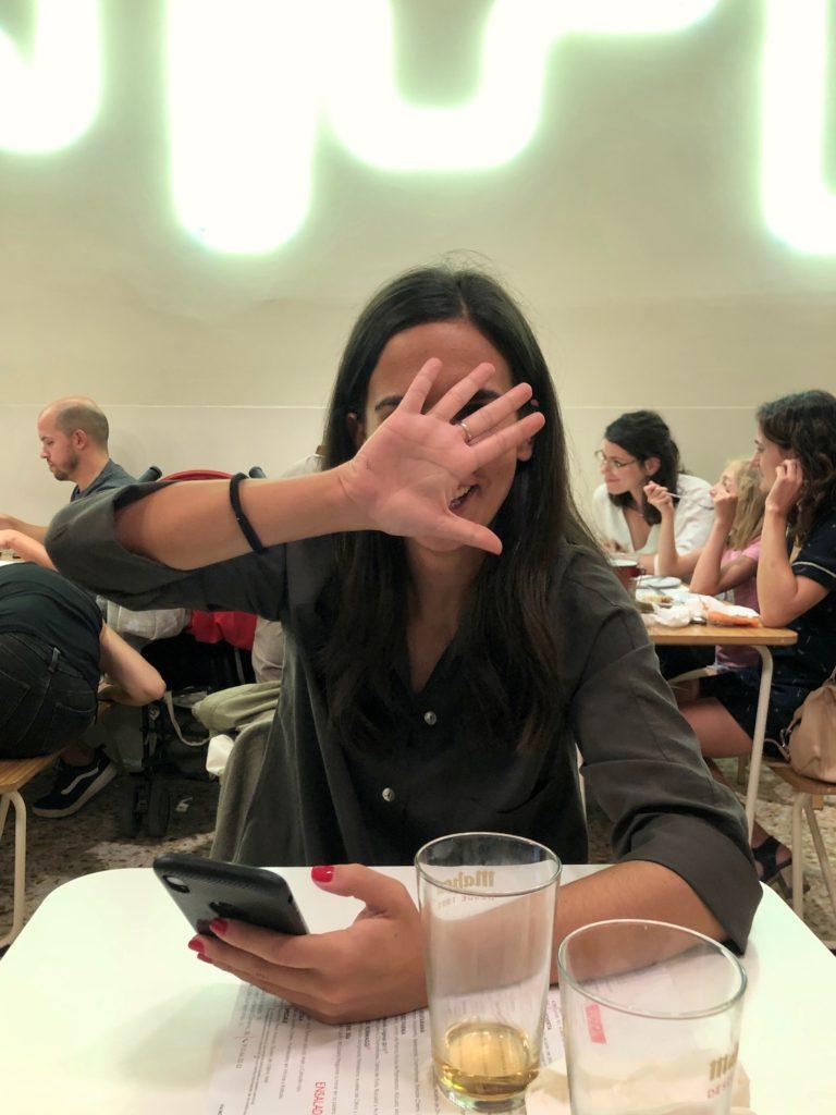 Elena hides behind her hand.