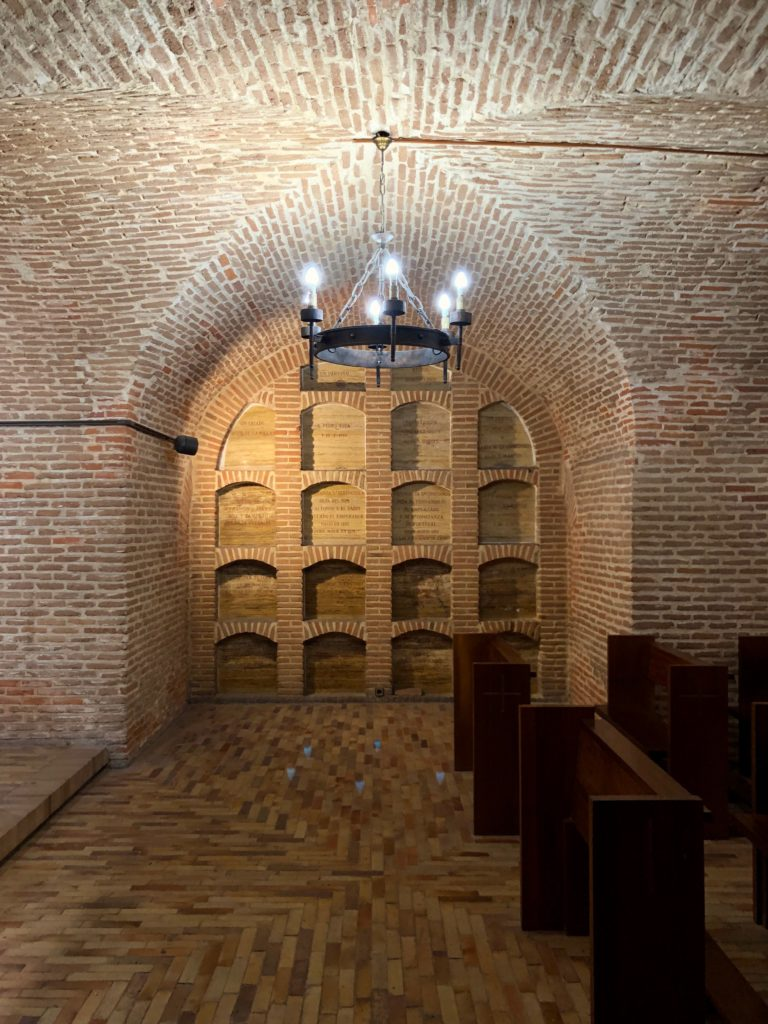 The inside of a Madrid crypt, with burial vaults, pews, arches, and a chandelier.