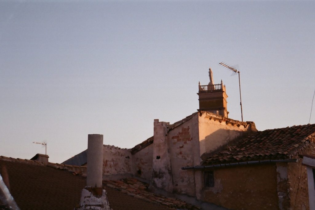 A film photo of sunlight setting on roofs and a church.