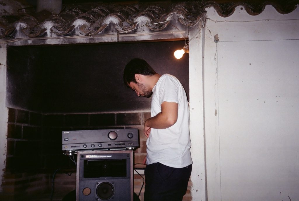A film photo of Roberto setting up a speaker system.