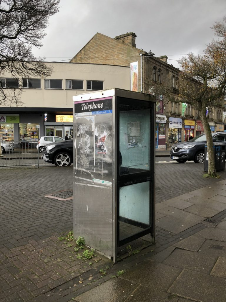 An old phone box in Burnley on a wet, cloudy day.
