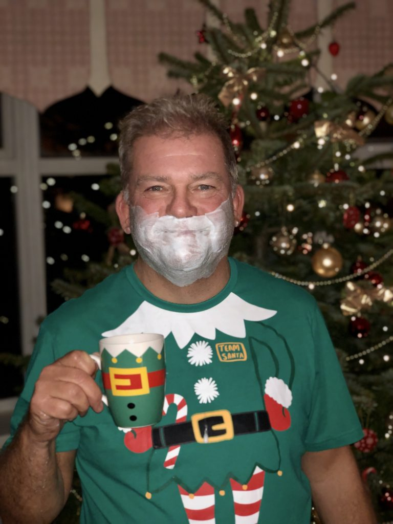 My dad with a beard of shaving foam, an elf mug and t-shirt, and our Christmas tree in the background.