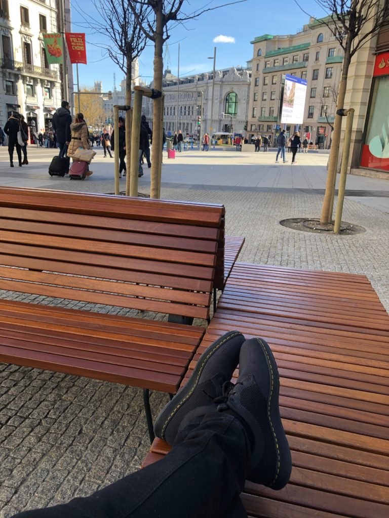 I lie on a street bench in Madrid.