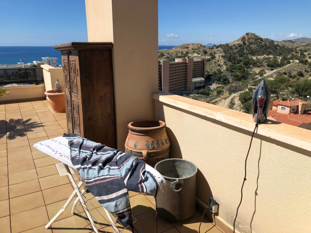 An ironing board set up on a terrace overlooking the sea.