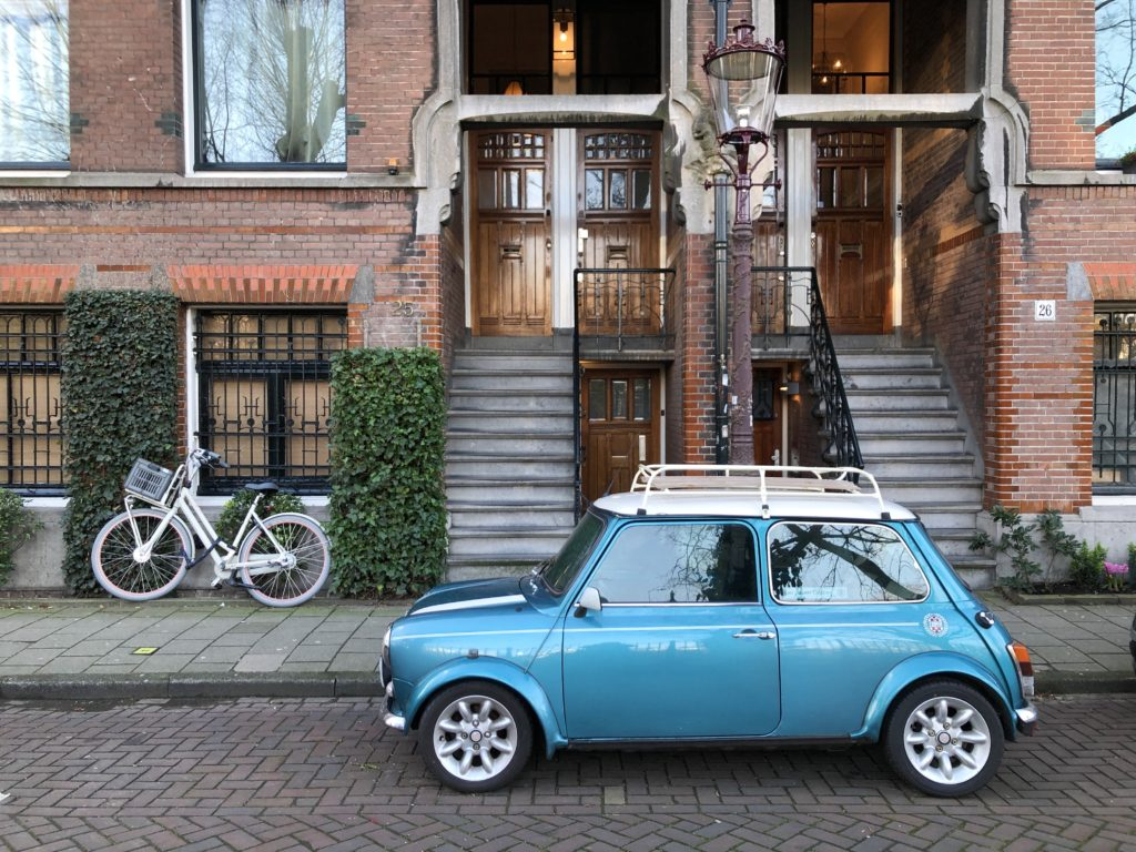 A Mini Cooper, a bicycle, and an old gas lamp in front of old red brick houses in Amsterdam.