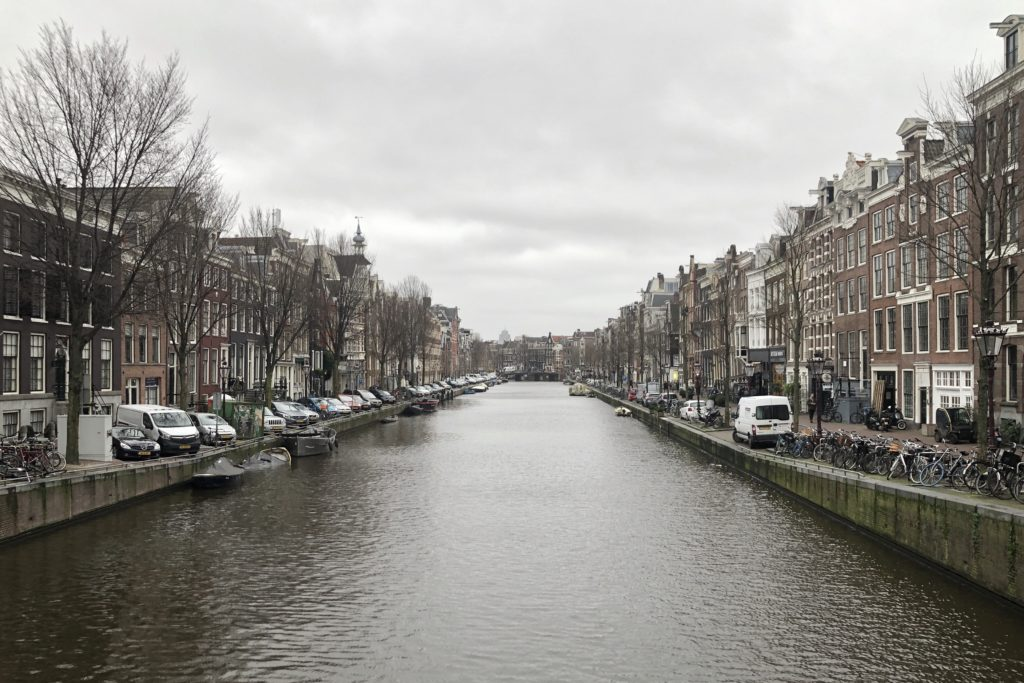 A canal and streets in the centre of Amsterdam, set below a grey sky.