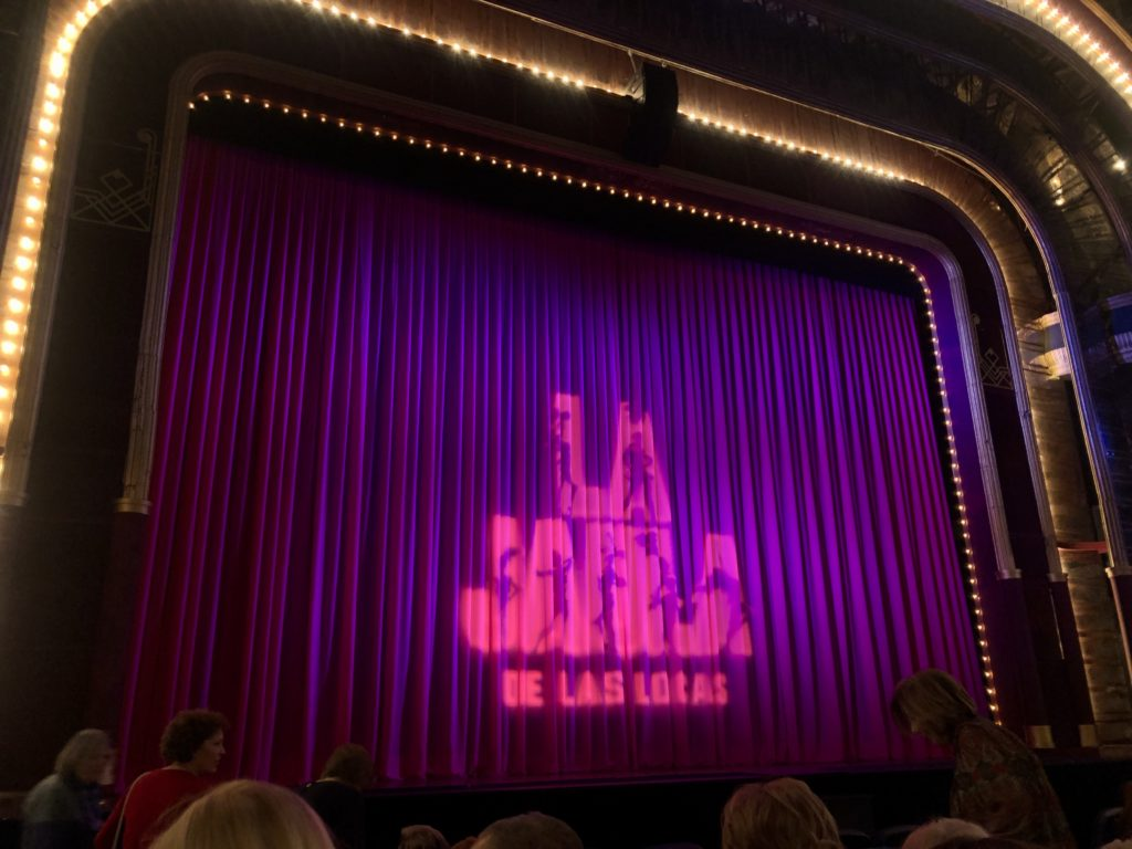 "A curtain on a stage reads ""La jaula de las locas""."