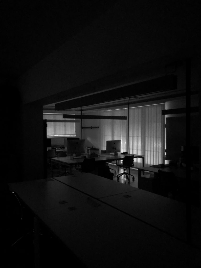 The profiles of computers are seen in a darkened office.