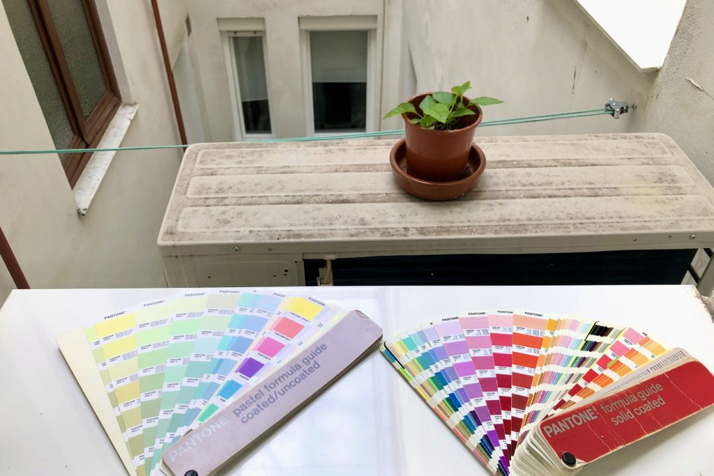 Pantone swatches sit on a windowsill with an apple plant growing on top of an air conditioning unit.