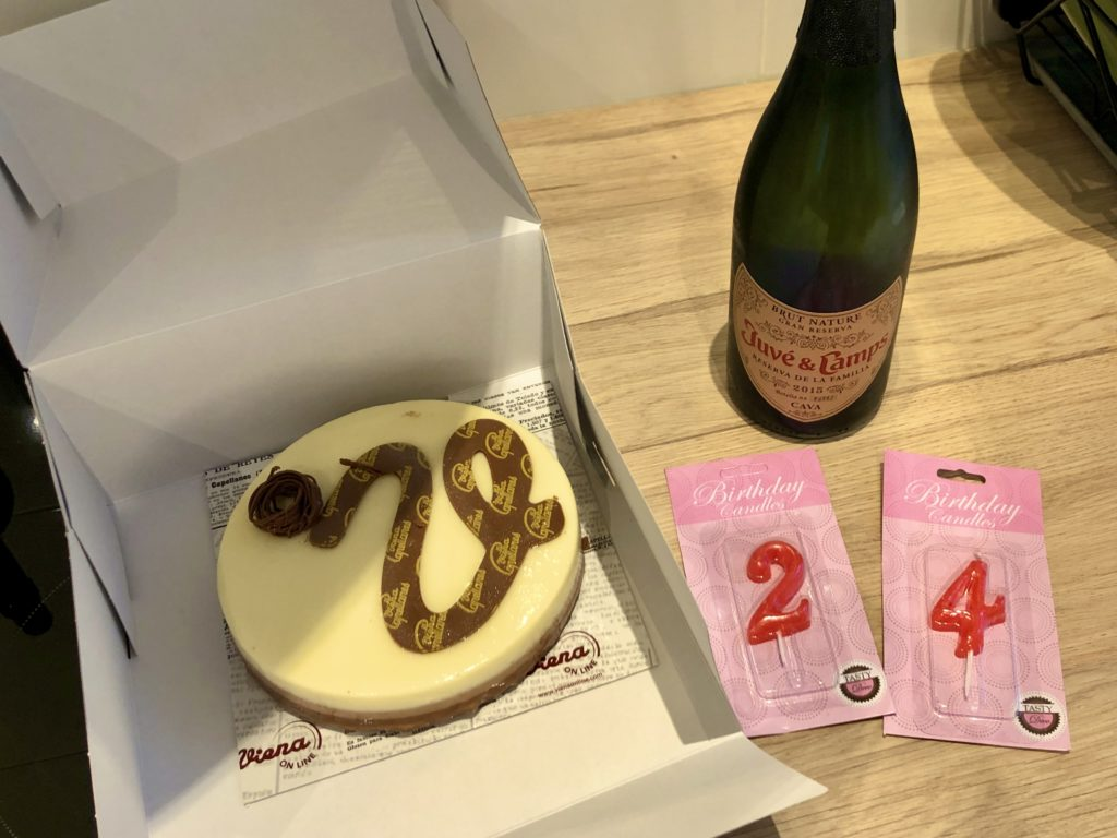 "A cake, candles reading ""24"", and a bottle of cava."