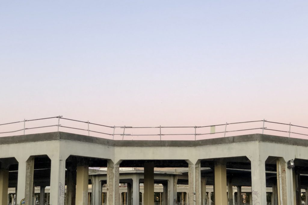 A pastel blue and pink sky sets over the concrete shell of a large structure.