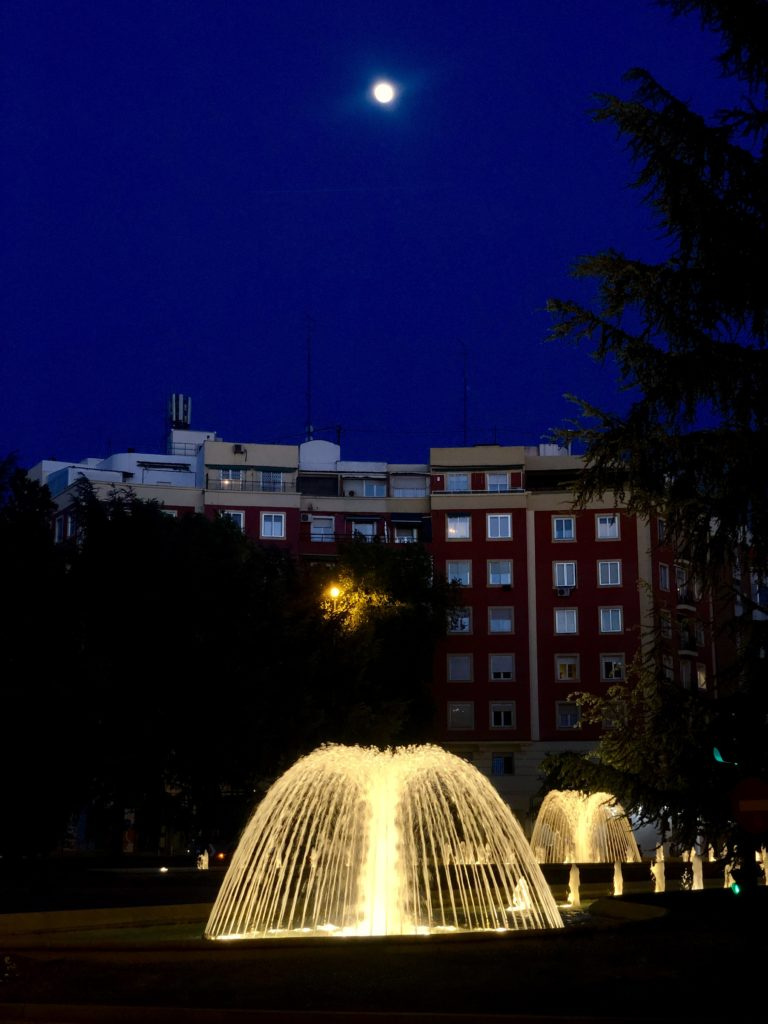 A series of illuminated fountains in Madrid below a full moon sky.