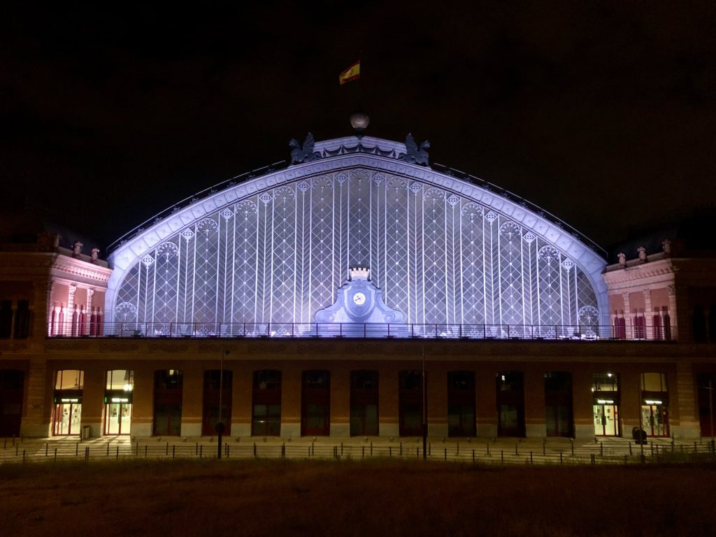 The Atocha train station lit up at night.