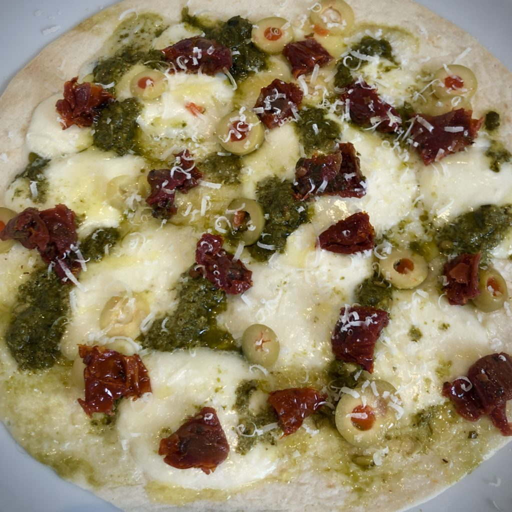 An Italian-style flatbread covered in mozzarella, pesto, dried tomato, olives, and parmesan.