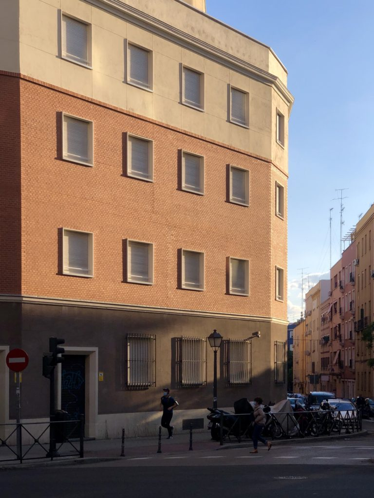 The evening sun illuminates the facade of a redbrick building in Madrid, Spain.