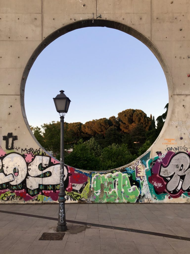 Trees and sky are seen through a circular hole in a concrete wall, with a streetlamp in the foreground.