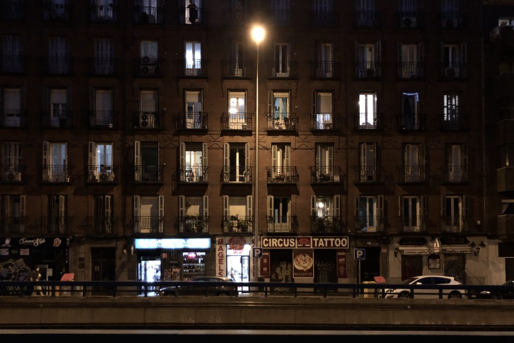 The brick facade of a building near the Atocha Train Station in Madrid. A streetlight lights up part of the dark facade by night.