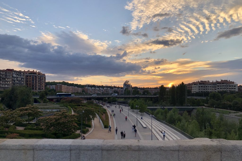 The evening sky full of various cloud formations seen from a bridge over the river in Madrid.