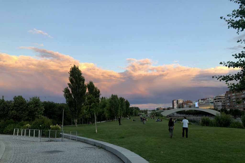 The sunset in Madrid colours a cloud formation in orange in contrast with the blue sky.