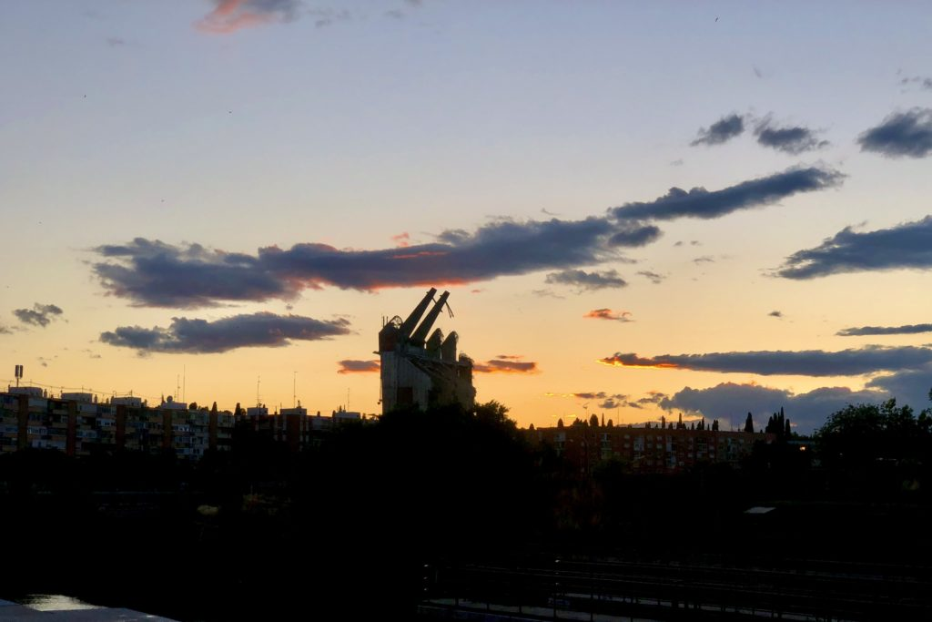 The silhouette of the nearly demolished Vicente Calderón stadium in Madrid, against a sunset.
