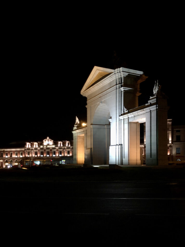 The arch next to a train station in Madrid lit up at night.