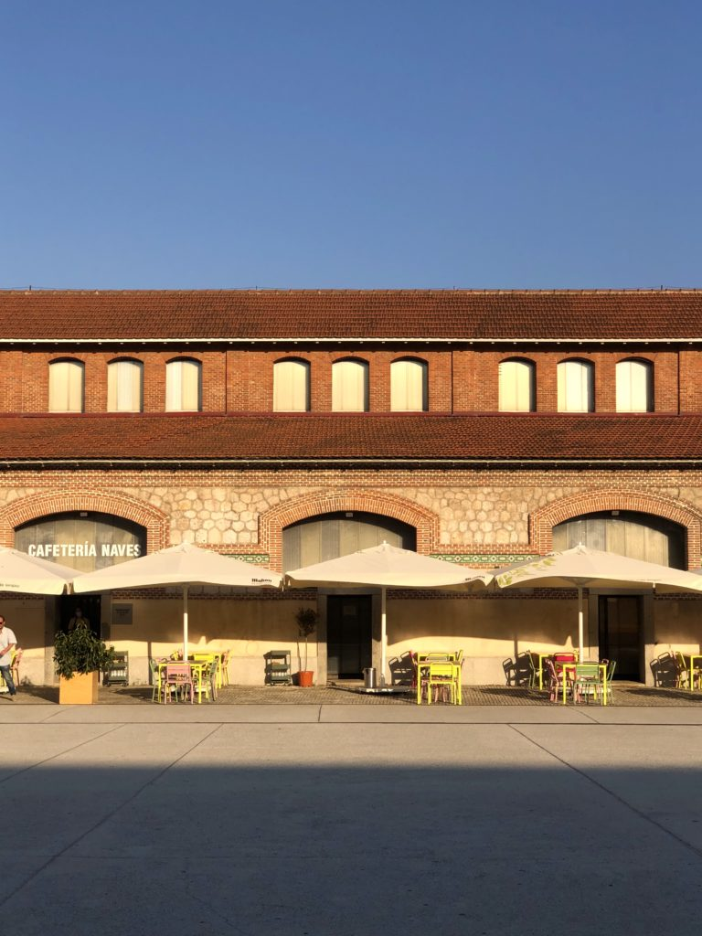 One of the buildings of the Matadero in Madrid in the evening sun with a terrace in the foreground.