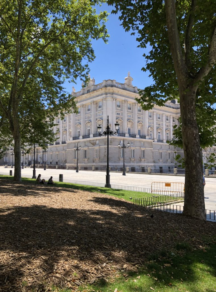 The royal palace of Madrid is visible through the trees of the Plaza del Oriente.