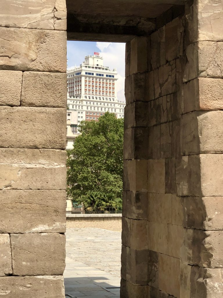"The ""Building of Spain"" hotel seen through one of the arches of the Debod Temple in Madrid, Spain."