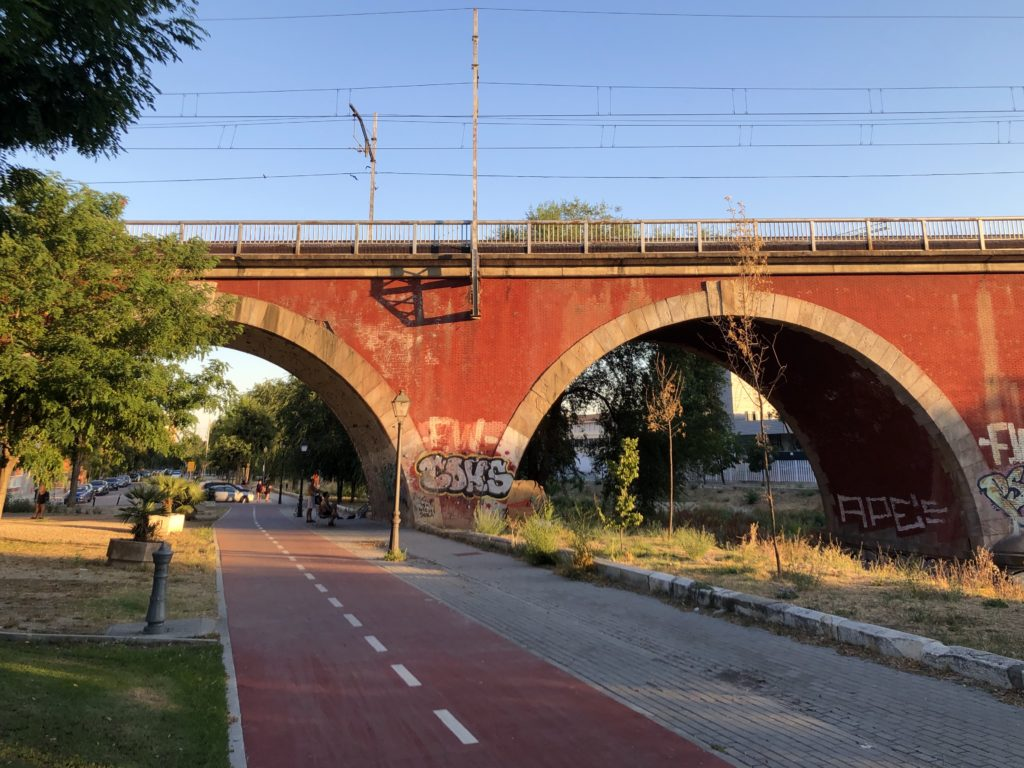 A red railway overpass is lit in the warm glow of the evening sun in Madrid, Spain.