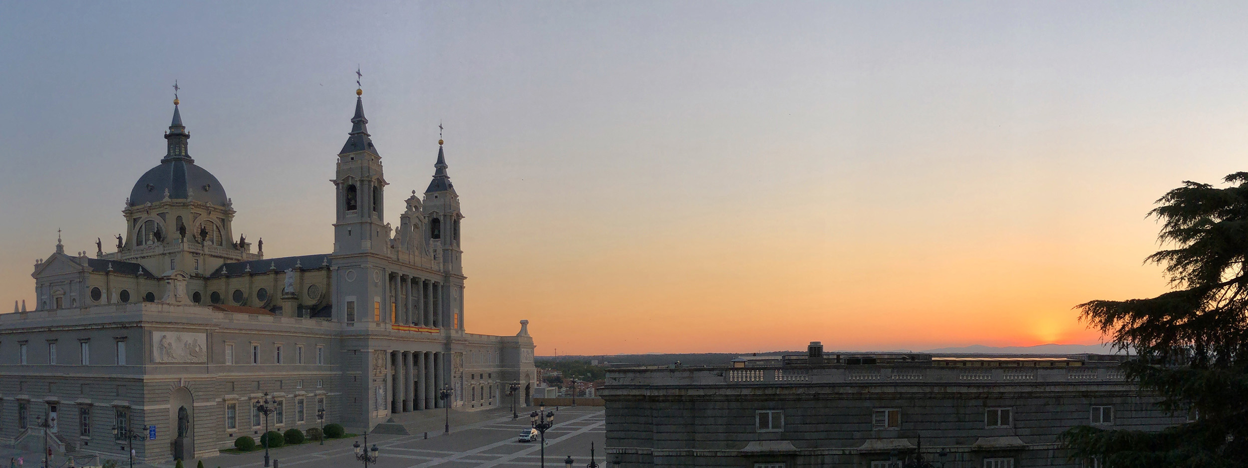 A panorama of a sunset over the royal palace and cathedral of Madrid.