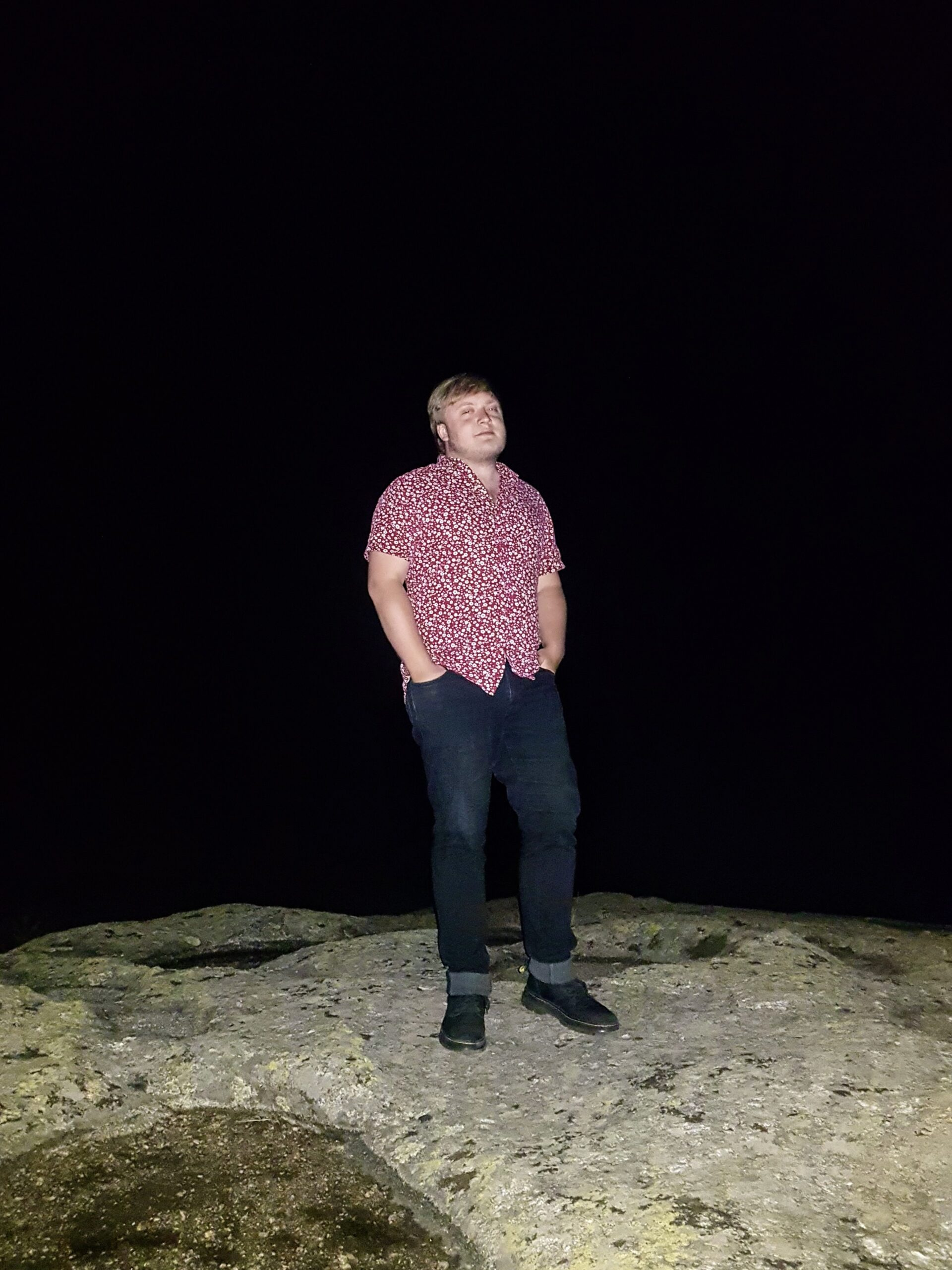 I stand on a rock in the darkness.