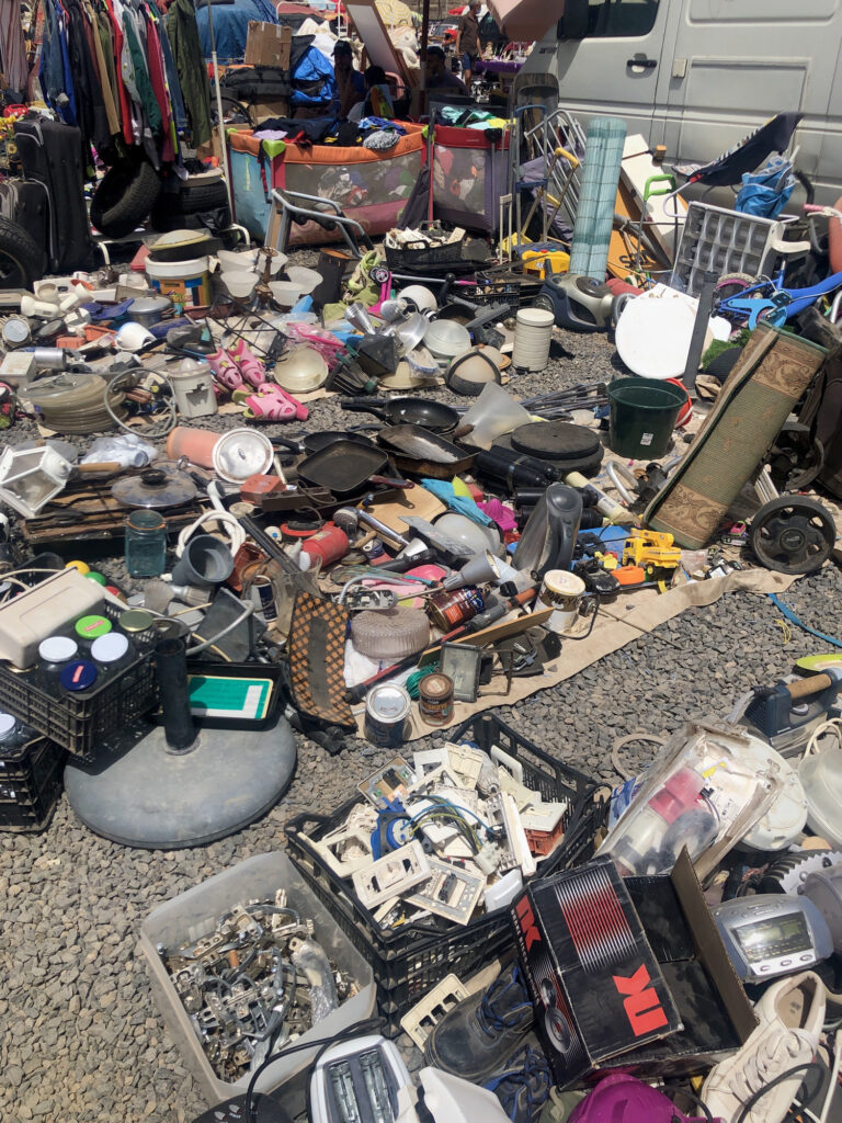 A selection of goods on the floor of a car boot sale.