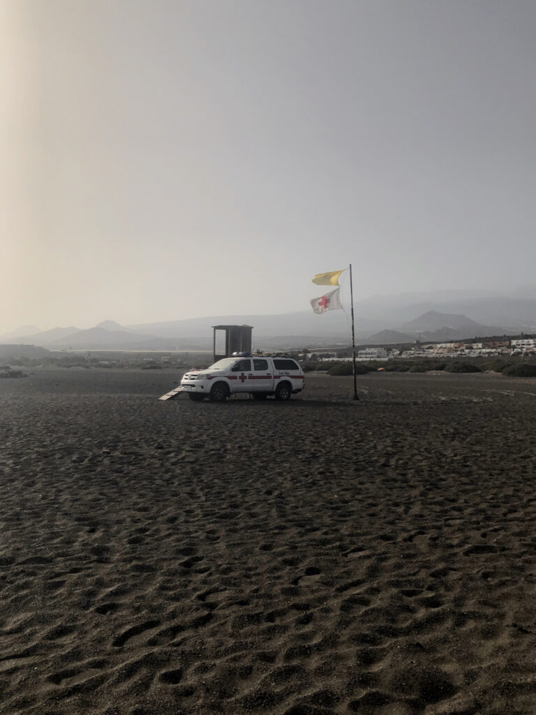 A lifeguard's car and flags on a beach with fog in the background.