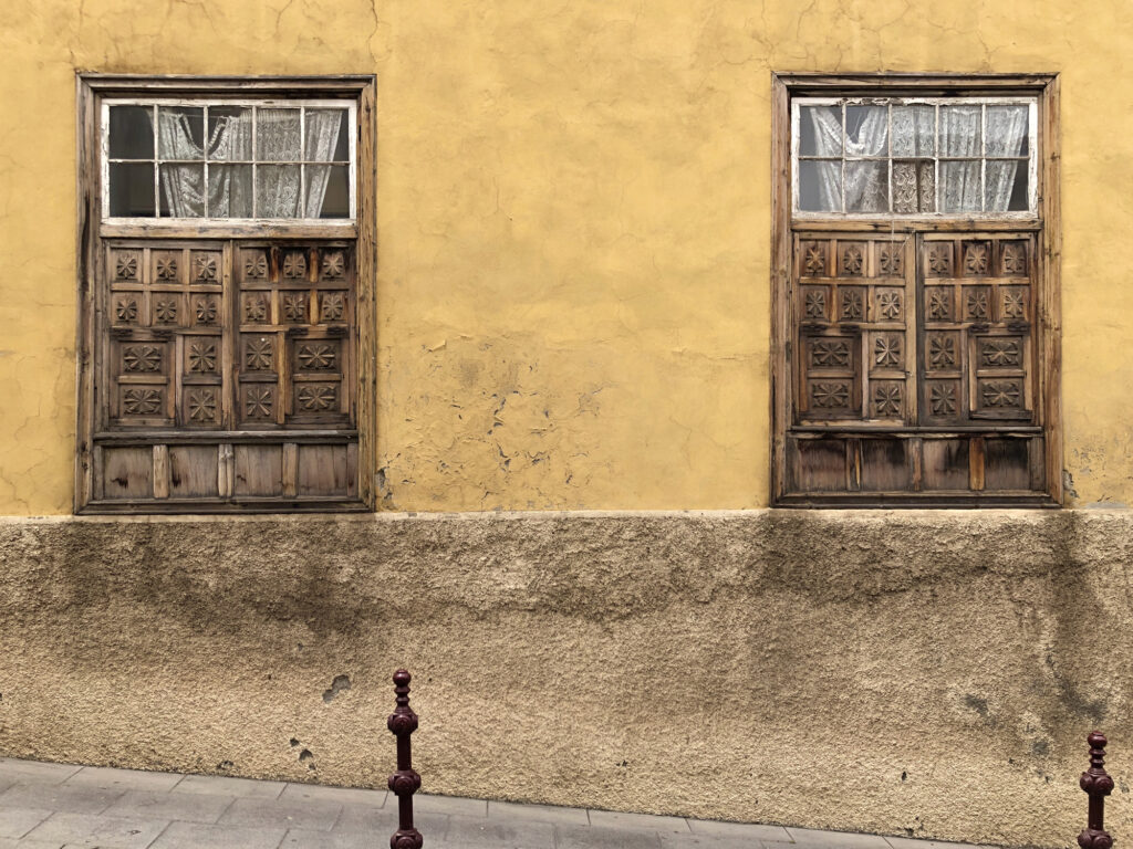 Two old wooden windows on a yellow plaster wall.