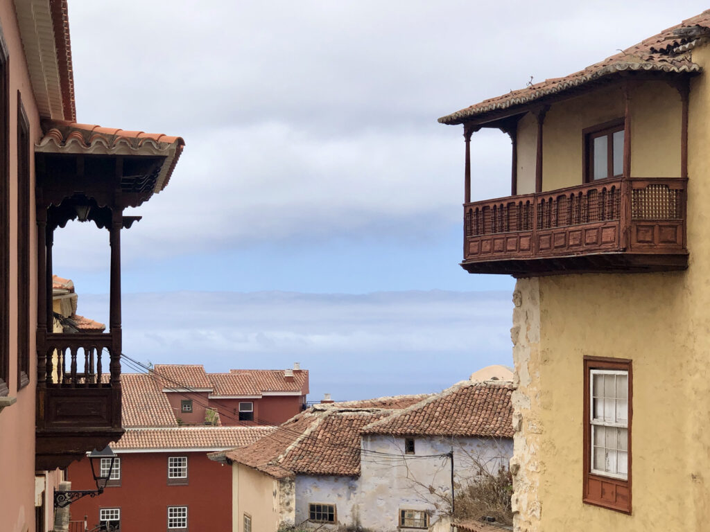 The sea and clouds between two old houses with wooden balconies.