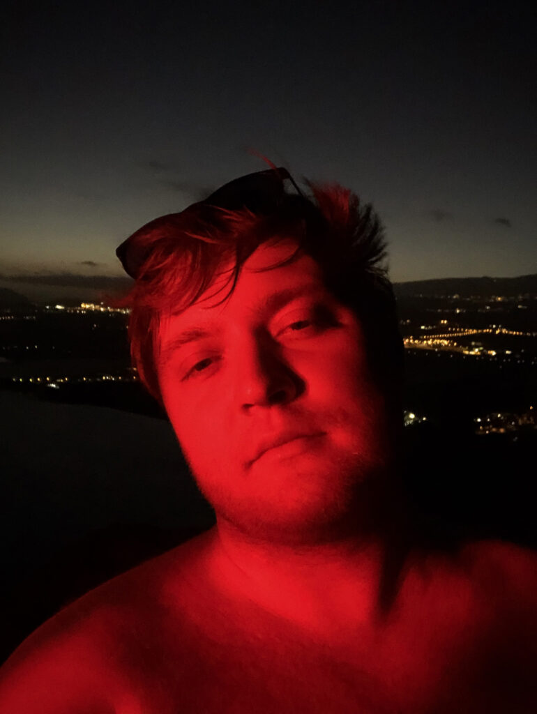 A selfie taken with Tenerife by night in the background. I am illuminated in red.