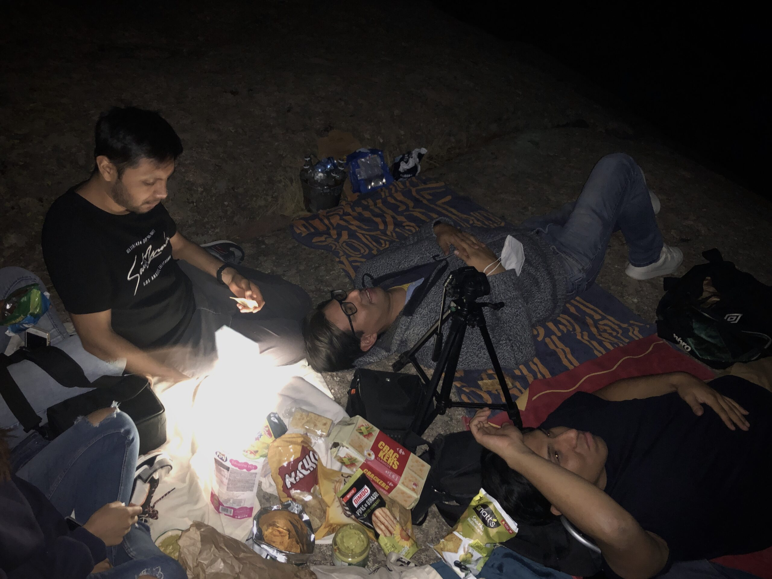 A group of friends lying on a rock in the dark.