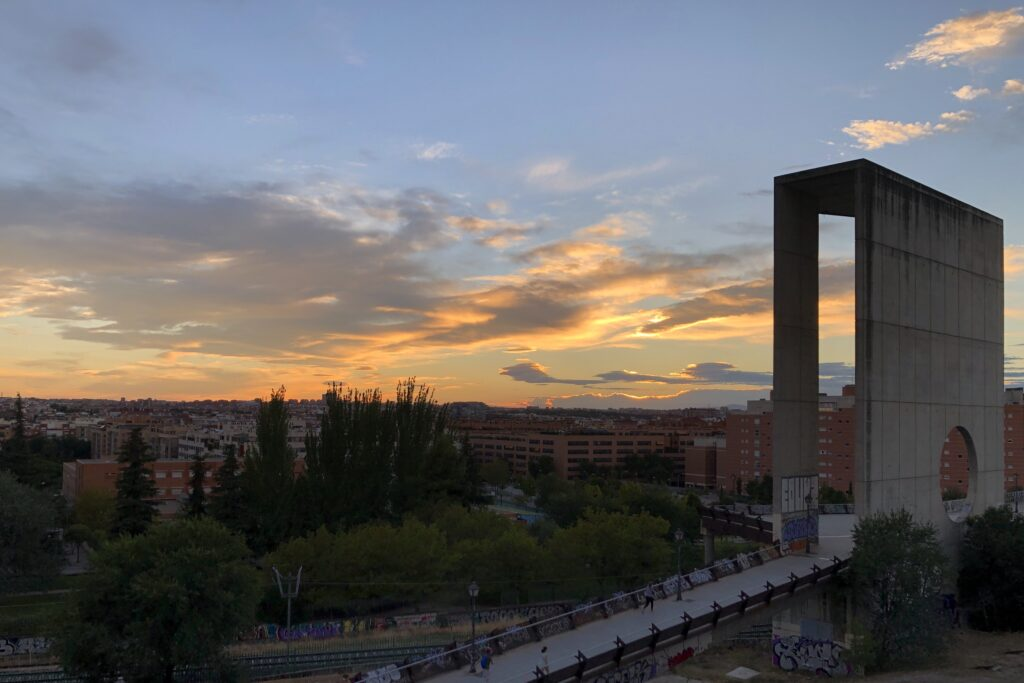 A sunset with orange clouds behind a large concrete structure over Madrid.