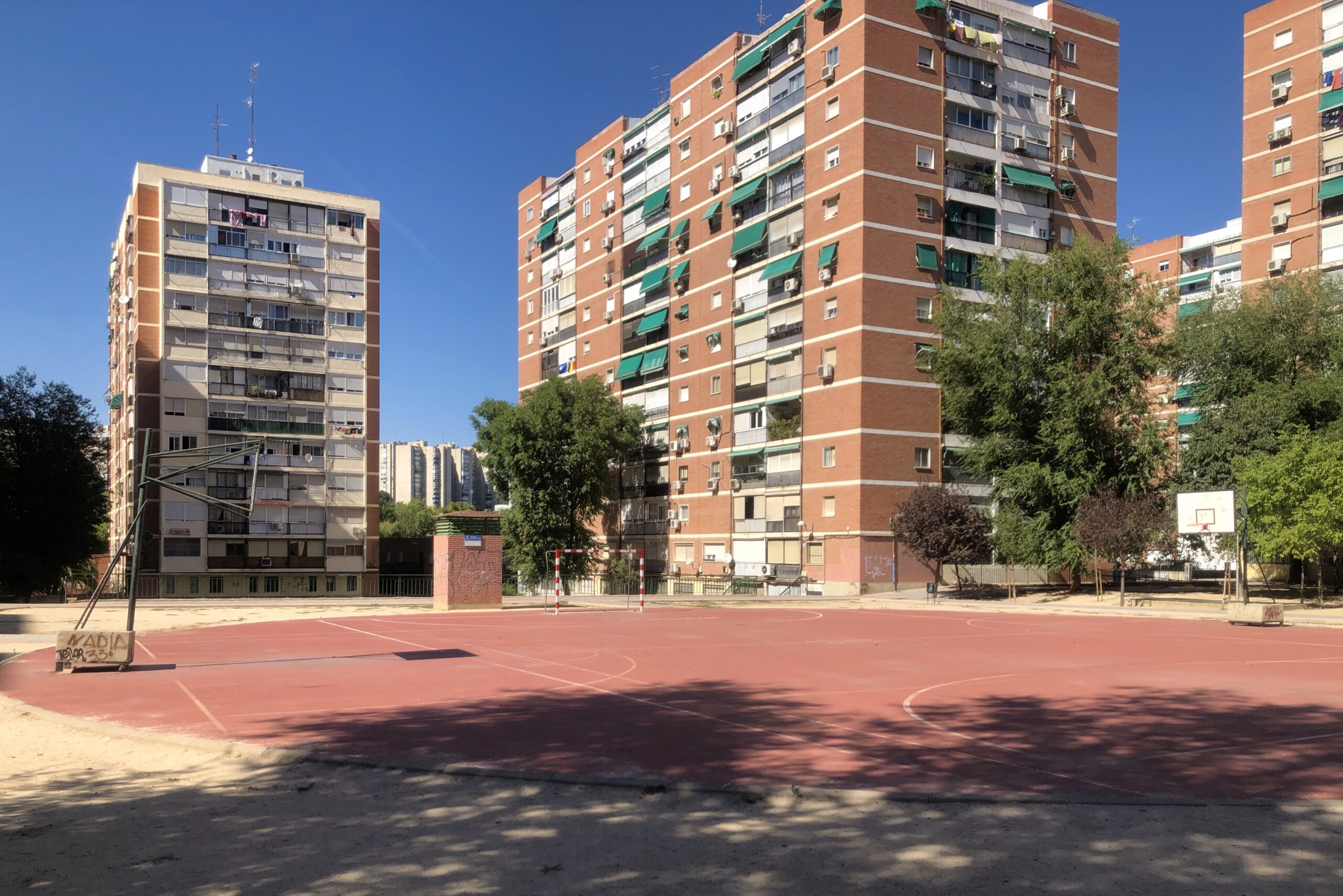 A baseball court in between blocks of flats.