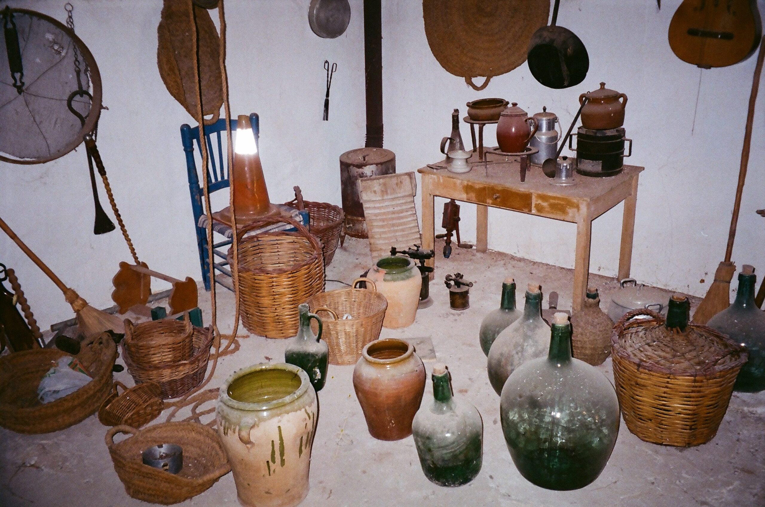 A series of pots, wicker jars, and glass bottles covered in dust in the corner of the loft of an old house.