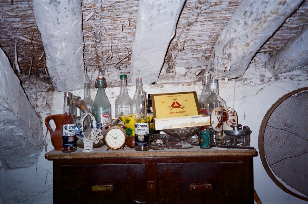 An old chest of drawers is littered with empty glass bottled, boxes, and an old alarm clock, all covered in dust and perched below an old wooden roof.