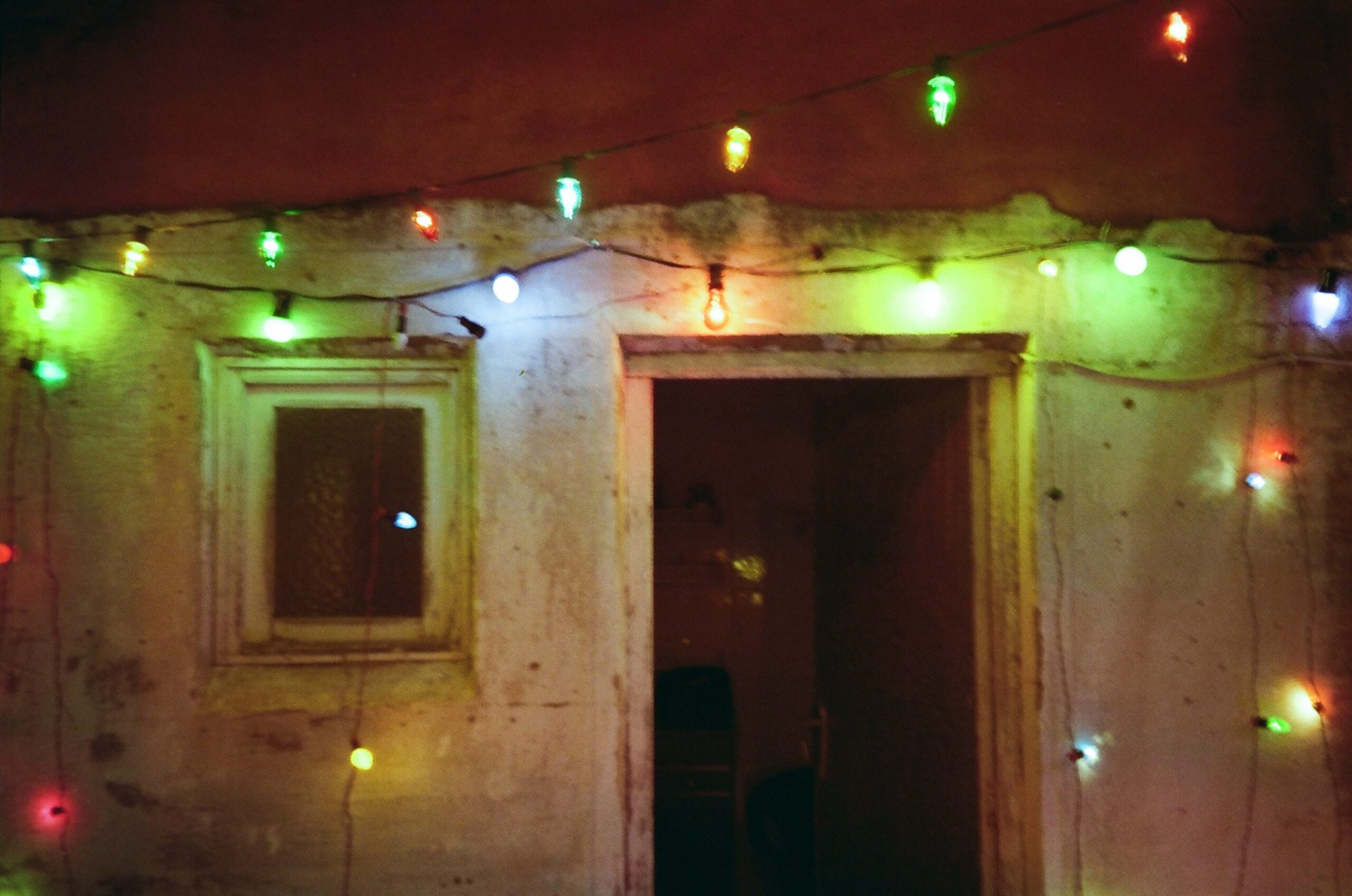 A series of coloured lights adorn the old entrance to an outdoor bathroom.