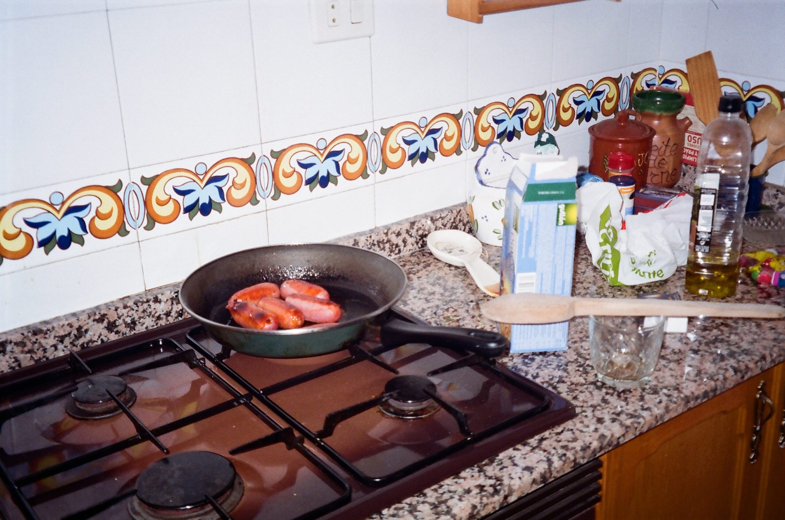 Chorizo sausages cook in a pan on an old gas stove.