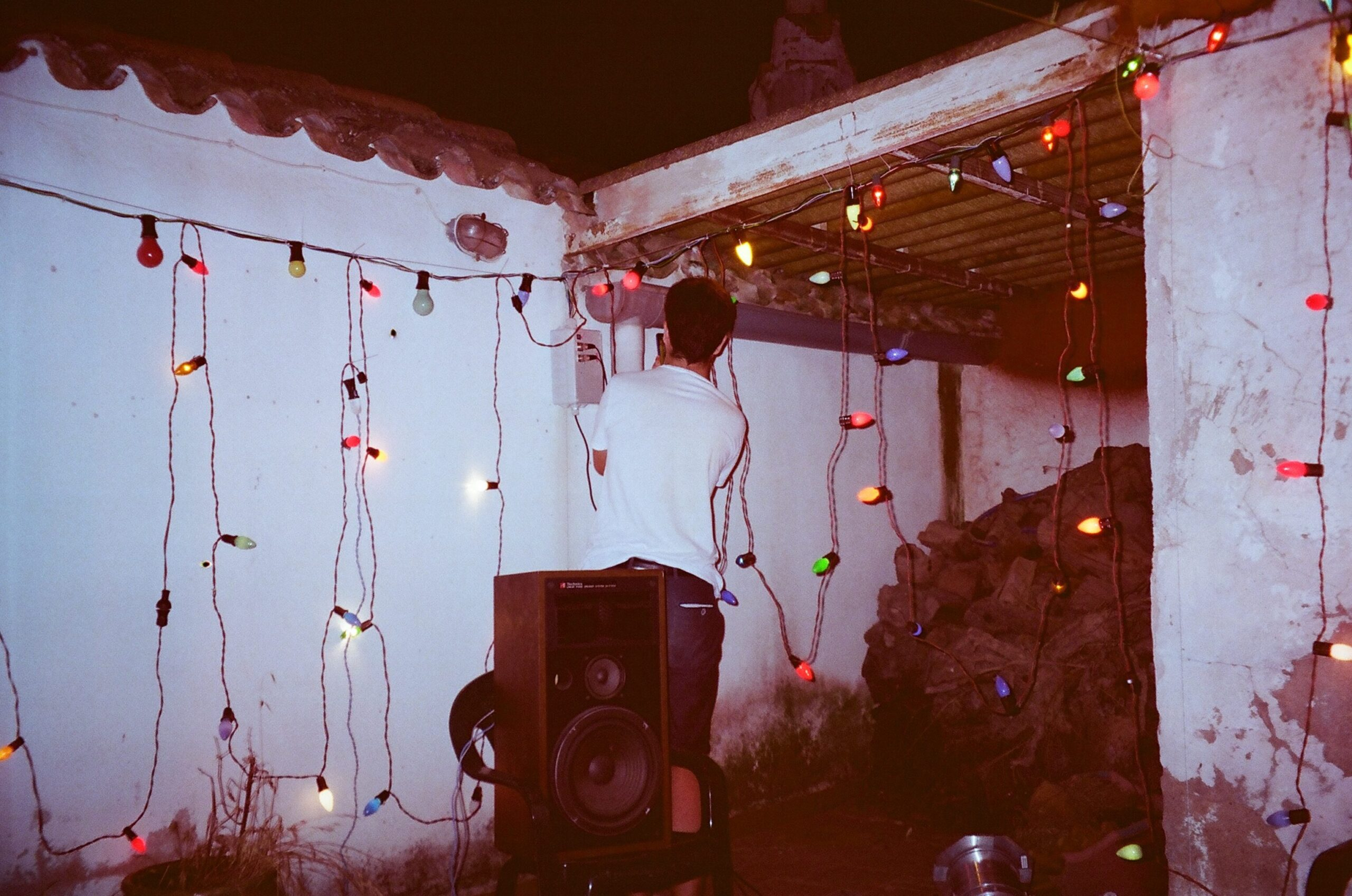 Roberto sets up a series of coloured fairy lights in the corner of an old patio.