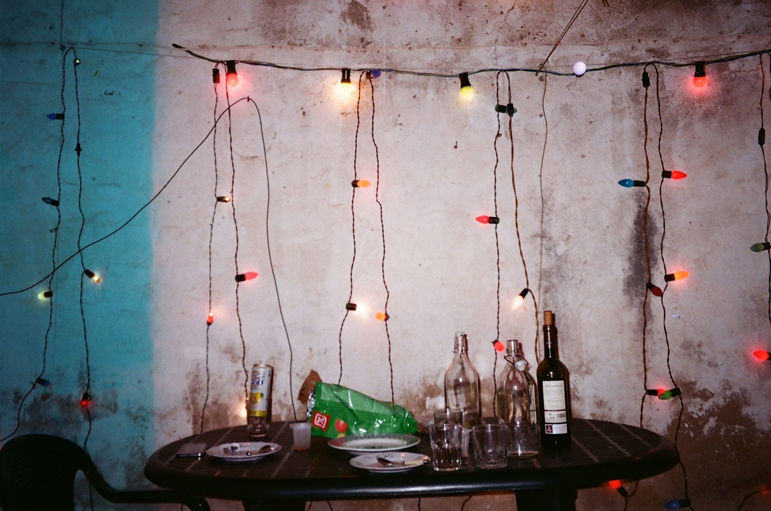 A series of fairy lights hang on an old wall behind a table covered in empty bottles and plates.