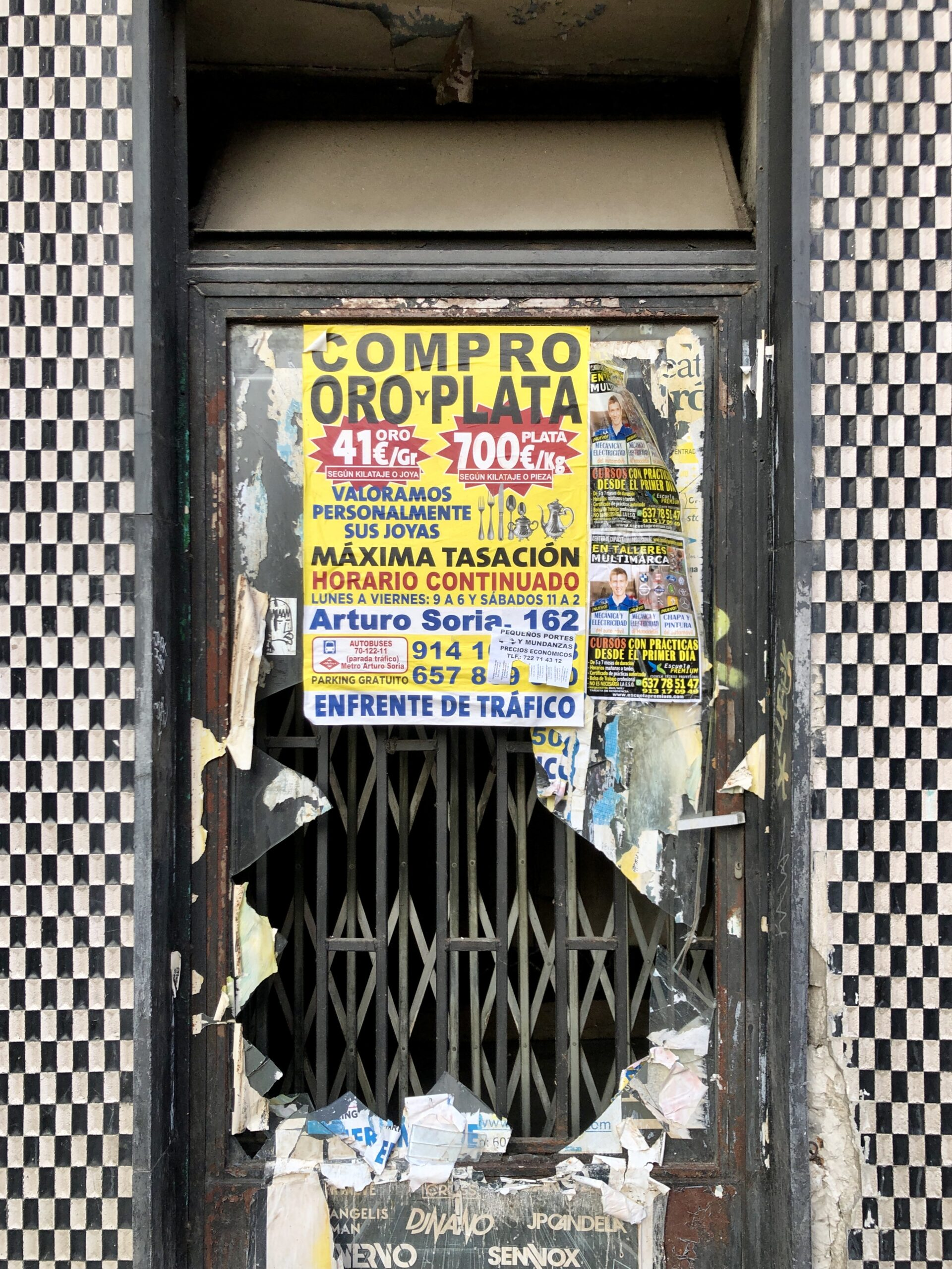 A door surrounded by a checkerboard design with broken glass and covered in posters.